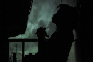silhouette of woman watching a storm from her window