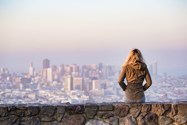 blond sitting on stone wall watching cityscape